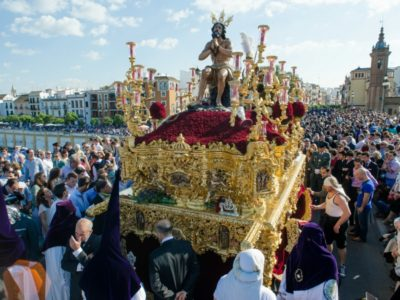 """SEVILLE. SPAIN - APRIL 13: The brotherhood of """"La Estrella"""" In their procession by Seville crossing the bridge of Triana, In Holy week on april 13, 2014 in seville."""