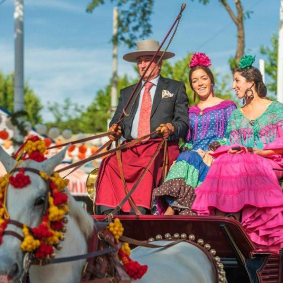 dos mujeres vestido de flamenco en un coche de caballo en la feria de Sevilla